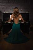 Schönheitsfrau im Abendkleid, das Klavier spielt Stockfotografie