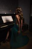 Schönheitsfrau im Abendkleid, das Klavier spielt Stockfoto