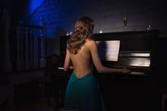 Schönheitsfrau im Abendkleid, das Klavier spielt Lizenzfreie Stockbilder