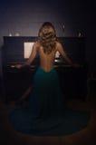 Schönheitsfrau im Abendkleid, das Klavier spielt Lizenzfreies Stockfoto