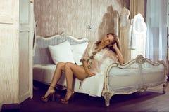 Schönheitsfrau im Bett im weißen Innenraum Stockfotografie