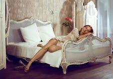 Schönheitsfrau im Bett im weißen Innenraum Stockfotos