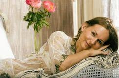 Schönheitsfrau im Bett im weißen Innenraum Stockbilder
