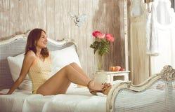 Schönheitsfrau im Bett im weißen Innenraum Lizenzfreie Stockfotografie