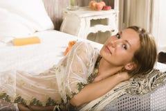 Schönheitsfrau im Bett im weißen Innenraum Stockfoto