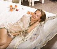 Schönheitsfrau im Bett im weißen Innenraum Lizenzfreies Stockbild