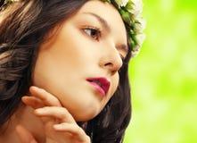 Schönheitsfrau mit Blume auf Grün Lizenzfreie Stockfotografie