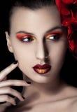 Schönheitsfrau mit Blumen auf schwarzem Hintergrund Lizenzfreies Stockfoto