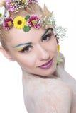 Schönheitsfrau mit Blumen im Haar betrachtet Sie Lizenzfreie Stockfotografie