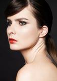 Schönheitsfrau mit den roten Lippen auf schwarzem Hintergrund Stockfotografie