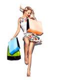 Schönheitsfrau mit Einkaufstaschen im kurzen weißen Kleid lizenzfreies stockbild