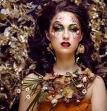 Schönheitsfrau mit Gesichtskunst und Schmuck von den Blumenorchideen Stockfotos