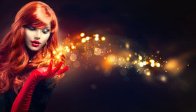 Schönheitsfrau mit goldener Magie funkt in ihrer Hand Lizenzfreies Stockfoto