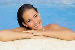 Schönheitsfrau mit perfekten Haut und den Zähnen in einem Pool stockbild
