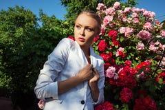 Schönheitsfrau mit rosafarbenen Blumen des Bündels Stockbild