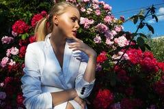 Schönheitsfrau mit rosafarbenen Blumen des Bündels Lizenzfreie Stockfotos