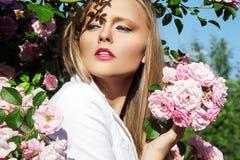 Schönheitsfrau mit rosafarbenen Blumen des Bündels Mode-blondes vorbildliches Porträt Stockfoto