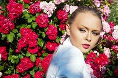 Schönheitsfrau mit rosafarbenen Blumen des Bündels Mode-blondes vorbildliches Porträt Lizenzfreies Stockbild