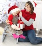 Schönheitsfrau und -kind an der Weihnachtsdekoration Lizenzfreie Stockfotos