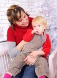 Schönheitsfrau und -kind an der Weihnachtsdekoration Stockfotos