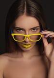 Schönheitsfrauen-Gesichtsporträt mit den gelben Lippen und den gelben Gläsern Stockfotografie