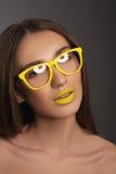 Schönheitsfrauen-Gesichtsporträt mit den gelben Lippen und den gelben Gläsern Stockbilder