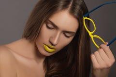 Schönheitsfrauen-Gesichtsporträt mit den gelben Lippen und den gelben Gläsern Lizenzfreies Stockbild