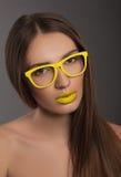 Schönheitsfrauen-Gesichtsporträt mit den gelben Lippen und den gelben Gläsern Stockfoto
