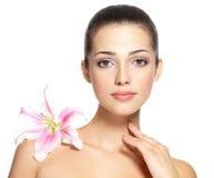 Schönheitsgesicht der jungen Frau mit Blume. Schönheitsbehandlungskonzept Lizenzfreies Stockfoto