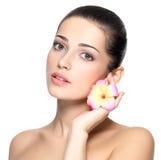 Schönheitsgesicht der jungen Frau mit Blume. Schönheitsbehandlungskonzept Lizenzfreies Stockbild