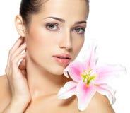 Schönheitsgesicht der jungen Frau mit Blume. Schönheitsbehandlungskonzept Stockbilder