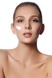 Schönheitsgesicht der jungen Frau Schönheitsgesicht der jungen Frau mit kosmetischer Sahne auf einer Backe Nahaufnahmeportrait ge stockfotografie