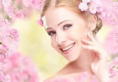 Schönheitsgesicht der jungen glücklichen Schönheit mit rosa Blumen herein Lizenzfreies Stockfoto