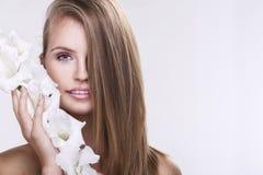 Schönes Gesicht der jungen schönen Frau mit Blume Lizenzfreie Stockfotos