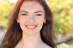 Schönheitsgesicht einer jungen lächelnden Frau draußen stockbild