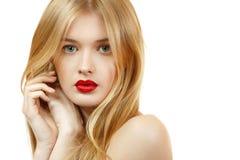 Schönheitsgesichtsnahaufnahme mit dem langen blonden Haar und klarem Rot Stockfotografie