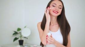 Schönheitsgesichtssorgfalt Das Porträt der jungen Frau mit der perfekten Haut, die Creme auf ihrer Haut aufträgt stock video