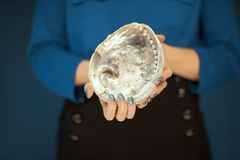 Schönheitshände mit dem perfekten blauen Nagellack, der Ohrschneckenoberteil hält stockbilder