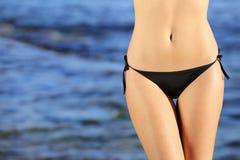Schönheitshüften mit einem Bikini auf dem Strand Stockbild