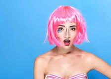 Schönheitshauptschuß Überraschte junge Frau mit kreativer Pop-Art bilden und zacken die Perücke aus, welche die Kamera auf blauem Stockbilder