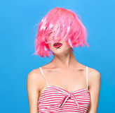 Schönheitshauptschuß Junge Frau mit kreativer Pop-Art bilden und zacken die Perücke aus, welche die Kamera auf blauem Hintergrund Lizenzfreies Stockfoto