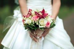 Schönheitshochzeitsblumenstrauß Braut ` s in Händen, im Abschluss- oben, im Blumenstrauß von pion-förmigen Rosen und im Ranunculu Stockbilder
