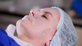 Schönheitsklinik Creme erhält auf junger Frau des Gesichtes trocken stock video