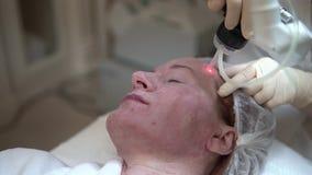 Schönheitsklinik Kosmetikerhände in den Handschuhen, die Gesichtsalterneinspritzung in einer weiblichen Haut machen Botox Kollage stock footage