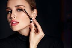 Schönheitskosmetik Frau, die schwarze Wimperntusche auf lange Wimpern setzt lizenzfreie stockfotos