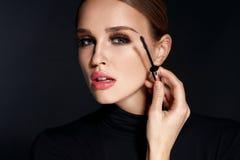 Schönheitskosmetik Frau, die schwarze Wimperntusche auf lange Wimpern setzt stockfoto