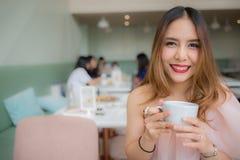 Schönheitslächeln und Halten eines Tasse Kaffees in ihrer Hand an der Kaffeestube stockbild