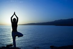 Schönheitsmädchen auf Strand in der Yogahaltung, entspannen sich Schattenbild Lizenzfreie Stockfotografie