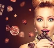 Schönheitsmädchen, das Schokolade isst Stockbild