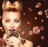Schönheitsmädchen, das Schokolade isst Stockbilder
